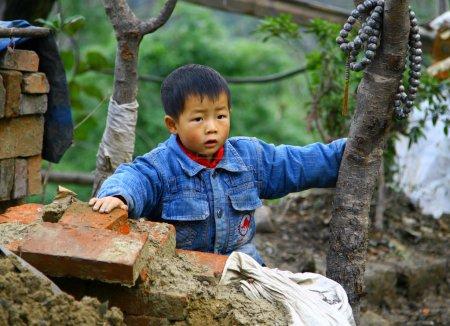 Photo pour Wudanshan, Chine - 1er novembre 2007: petit garçon asiatique sur un chantier de construction. selon les croyances traditionnelles chinois préfèrent les fils de soutien dans la vieillesse. ainsi, aujourd'hui, pour 100 filles représente plus de 120 garçons - image libre de droit