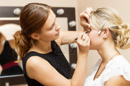 Woman applying make up for a bride in her wedding day near mirror