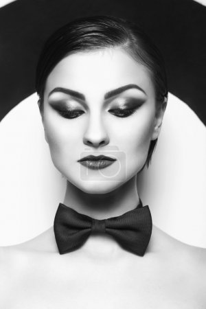 Pretty woman with evening make up and red lips in a bow-tie in a center of a dartboard background. Black and White