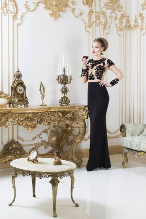 Beautiful blonde royal woman standing near retro table in gorgeous luxury dress looking in front of herself. Indoor