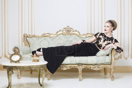 Beautiful blonde royal woman laying on a retro sofa in gorgeous luxury dress. Indoor. Copy Space