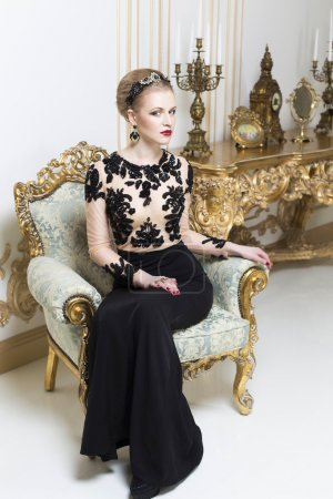 Beautiful blonde royal woman sitting on a retro chair in gorgeous luxury dress, looking at camera. Indoor