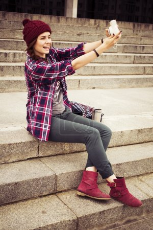 Brunette woman in hipster outfit sitting on steps and taking selfie on retro camera on the street. Toned image