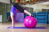 Přizpůsobit žena dělá cvičení s míčem na rohoži v tělocvičně usmívá