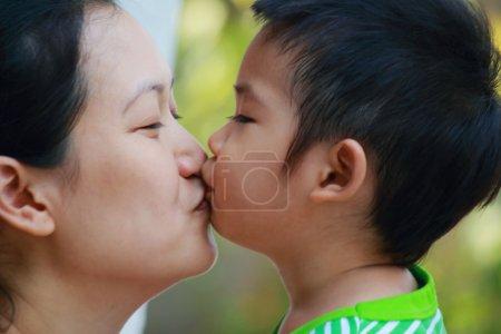 Photo pour Mère embrassant son enfant se bouchent - image libre de droit