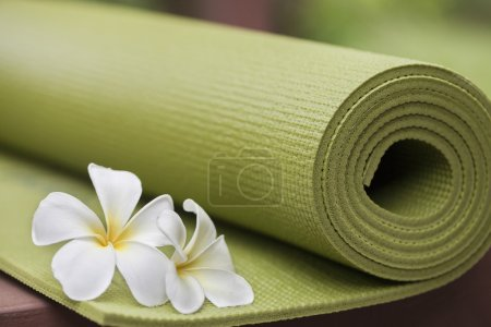 A green yoga mat with beautiful flowers...