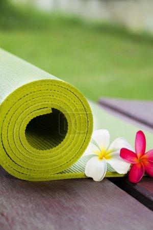 Photo pour Un tapis d'yoga est mis sur le sol de côté fleurs - image libre de droit