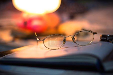 Vintage-Stillleben mit alten Brillen auf Buch neben Schreibtischlampe