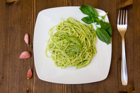 Spaghetti with pesto on wooden table