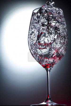 Wine glass filled with moving liquid splashes of red.