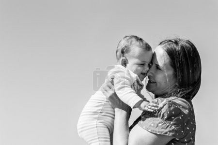 Mother and cute little baby girl on the beach