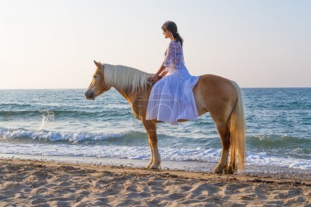 Photo for White dressed attractive young girl enjoys a romantic horse ride along a sandy shoreline in late afternoon mid summer sun. - Royalty Free Image