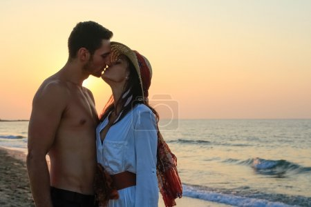 Happy young couple tenderly embracing and kissing at the beach at dusk.