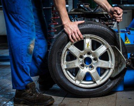 Photo pour Transportant des pneus, l'homme travaille avec pneu - image libre de droit