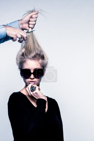 Fashion image of young woman loosing her hair in cutting of the world.