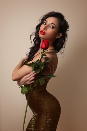 Sexy girl in little black dress with a red rose