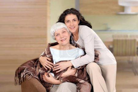 Photo pour Vieille femme et sa fille, assis sur une chaise avec couverture, câlin, mère, grand-mère - image libre de droit