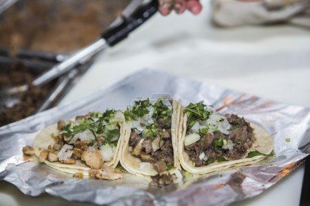Three freshly prepared carne asada tacos on foil...