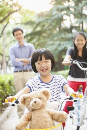 Foto de Hermanas montar sus bicicletas mientras los padres miran - Imagen libre de derechos