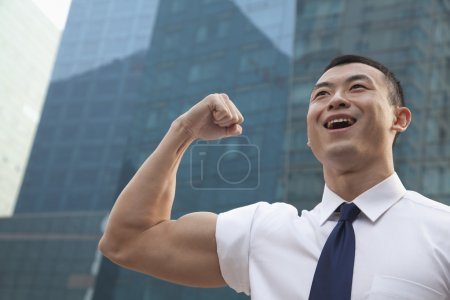 Young businessman flexing muscle