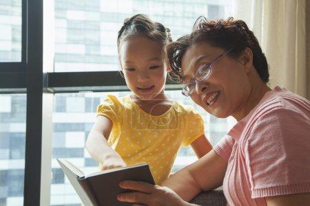 Photo pour Livre de lecture de grand-mère à sa petite-fille - image libre de droit
