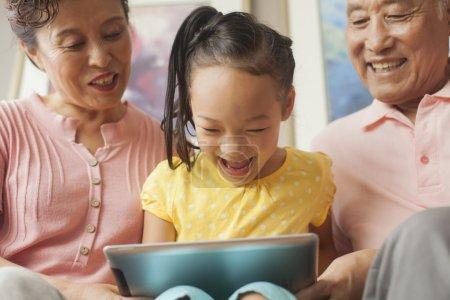 Photo pour Petite fille jouant avec les grands-parents - image libre de droit