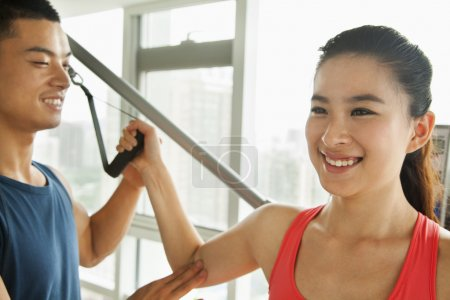 Young woman exercising with his personal trainer in the gym