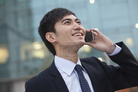 Businessman on the phone looking up