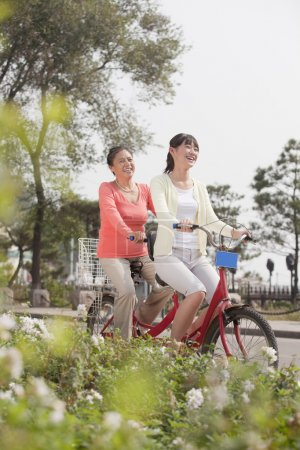 Grandmother and granddaughter riding tandem bicycle