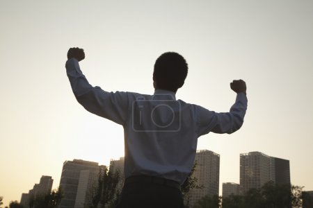 Photo for Young businessman with fists in the air celebrating - Royalty Free Image