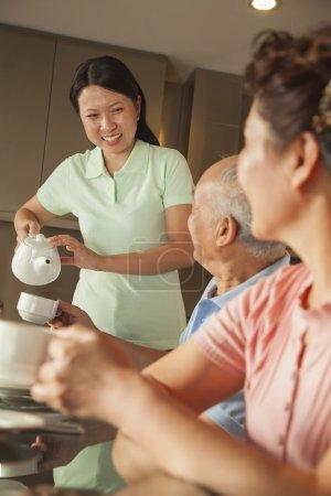Photo pour Parents avec fille adulte prenant son petit déjeuner - image libre de droit
