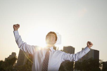 Photo pour Jeune homme d'affaires avec les poings en l'air célébrant - image libre de droit