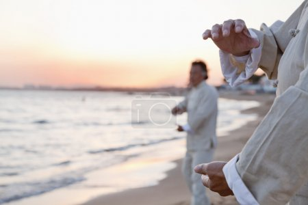 People practicing Taijiquan on the beach at sunset