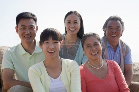 """""""Portrait of smiling multigenerational family sitting on the rocks outdoors"""