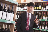 Young Man Choosing Wine in a Liquor Store