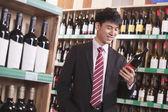 Joven elegir vino en una tienda de licores