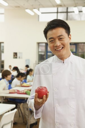 Chef in school cafeteria holding apple
