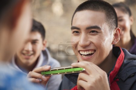 Photo for Young man using harmonica, portrait - Royalty Free Image
