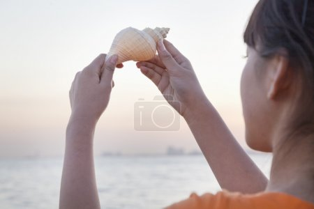 Teenage girl looking and holding up seashell