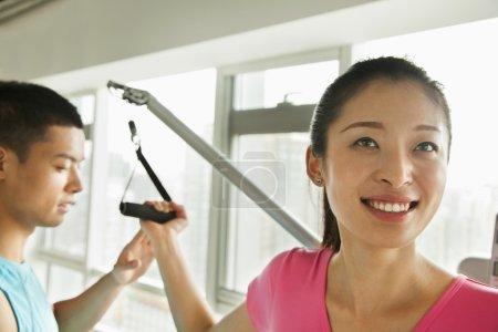 Foto de Mujer joven haciendo ejercicio con su entrenador personal en el gimnasio - Imagen libre de derechos