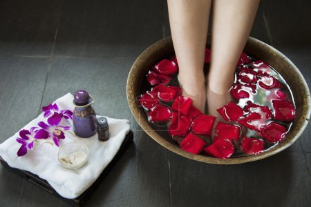 Woman's Feet in Water with Rose Petals