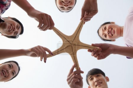 Group of Friends Holding a Starfish
