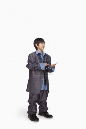 Boy dressed up as businessman using tablet