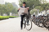 Businessman on a bicycle and reading the newspaper