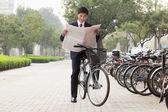 empresario en una bicicleta y leyendo el periódico