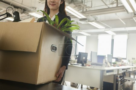 Businesswoman moving box with office supplies