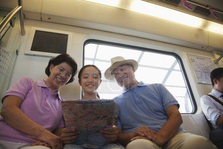 Photo pour Petite-fille avec grands-parents assis dans le métro et en regardant la carte - image libre de droit