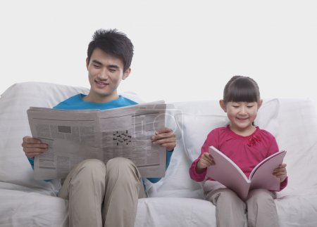 Photo for Father and daughter sitting on sofa reading separately, studio shot - Royalty Free Image