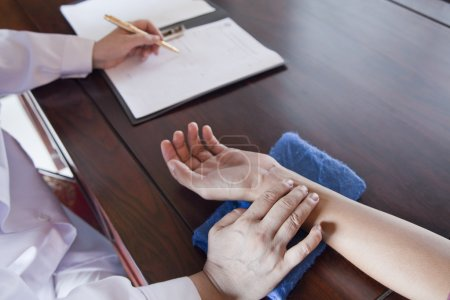 Patient's Hand While Doctor Takes Pulse