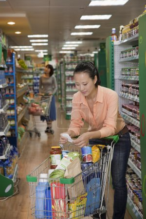 Photo for Woman looking at shopping list in supermarket - Royalty Free Image